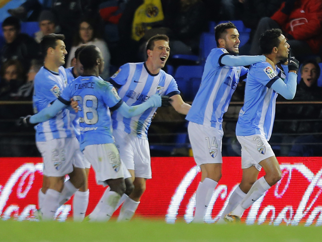 Malaga's Brazilian defender Weligton celebrates with his teammates after scoring during the Spanish league football match Villareal CF vs Malaga at El Madrigal stadium in Villarreal on November 29, 2013