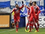 Lyon's Alexandre Lacazette celebrates with teammates after scoring his team's opening goal against Bastia during their Ligue 1 match on December 8, 2013
