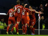 Liverpool's Luis Suarez is congratulated by teammates after scoring the opening goal against Norwich during their Premier League match on December 4, 2013