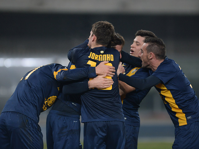 Hellas Verona's Jorginho celebrates with teammates after scoring his team's second goal against Atalanta during their Serie A match on December 8, 2013