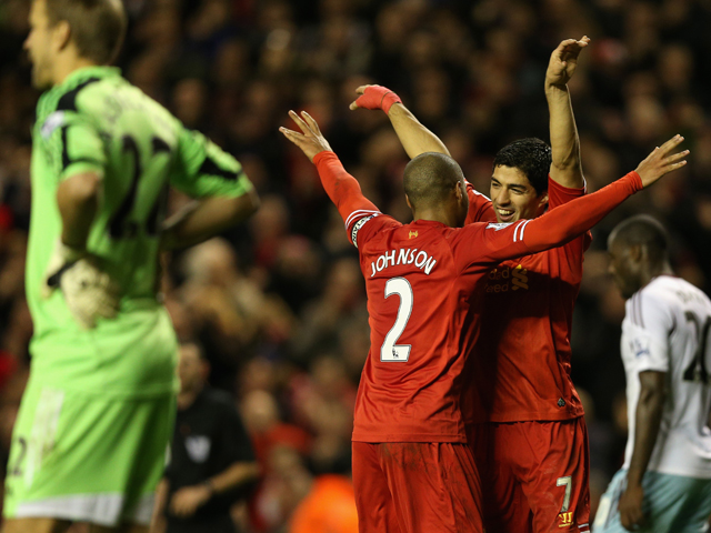 Luis Suarez of Liverpool celebrates scoring his team's third goal with team-mate Glen Johnson during the Barclays Premier League match between Liverpool and West Ham United at Anfield on December 7, 2013