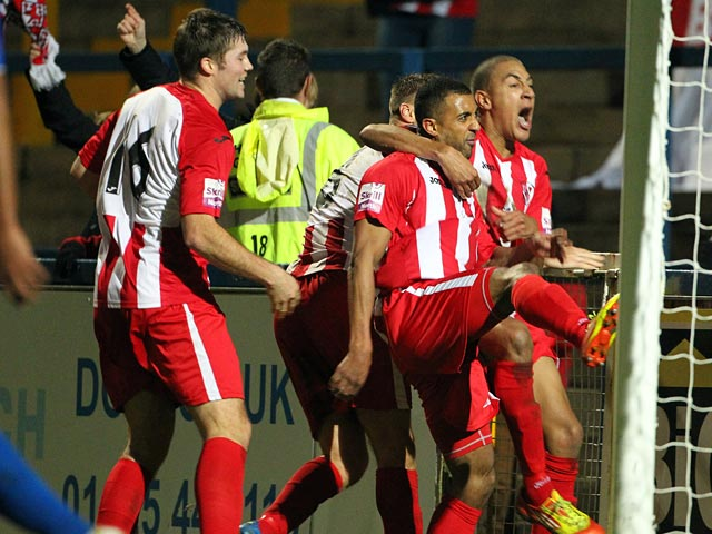 Brackley 's Owen Story celebrates with teammates after scoring his team's second goal against Macclesfield during their FA Cup match on December 7, 2013