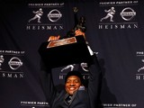 Jameis Winston, quarterback of the Florida State Seminoles, hoist the trophy during a press conference after the 2013 Heisman Trophy Presentation at the Marriott Marquis on December 14, 2013
