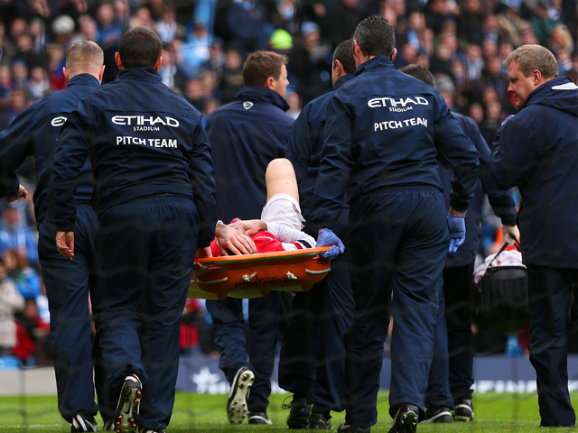 Laurent Koscielny of Arsenal is stretchered off during the Barclays Premier League match between Manchester City and Arsenal at Etihad Stadium on December 14, 2013