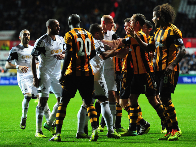 Swansea and Hull players clash during the Barclays Premier league match between Swansea City and Hull City at the Liberty Stadium on December 9, 2013