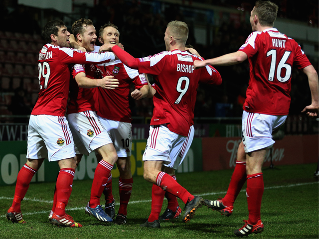 Joe Clarke of Wrexham AFC celebrates with team mates after scoring the first goal during the FA Cup Second Round match between Wrexham AFC and Oxford United at Racecourse Ground on December 9, 2013