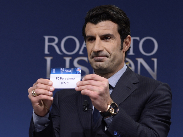 UEFA Champions League Final Ambassador, former Portuguese international footballer Luis Figo holds up the name of Barcelona during the draw for the last 16 of the UEFA Champions league tournament at the UEFA headquarters in Nyon on December 16, 2013