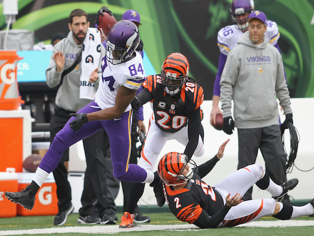 Cordarrelle Patterson of the Minnesota Vikings runs over Mike Nugent of the Cincinnati Bengals during their game at Paul Brown Stadium on December 22, 2013