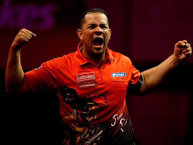 Devon Petersen of South Africa celebrates defeating Steve Beaton of England during his first round match on day four of the 2014 Ladbrokes.com World Darts Championships at Alexandra Palace on December 16, 2013