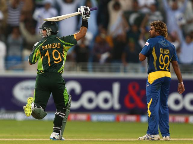 Batsman Shahzad Khan of Pakistan celebrates a century while bowler Lasith Malinga of Sri Lanka looks on during the second One Day International cricket match between Sri Lanka and Pakistan in Dubai on December 20, 2013