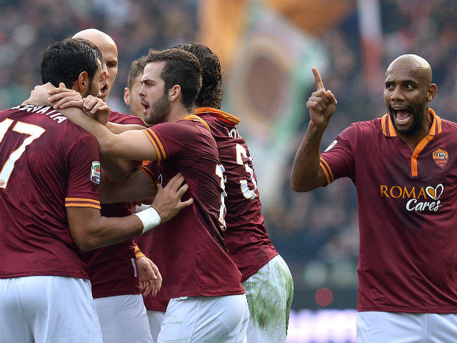 Roma defender Mehdi Menadia celebrates with teammates after scoring during the Italian Serie A football match As Roma vs Catania on December 22, 2013