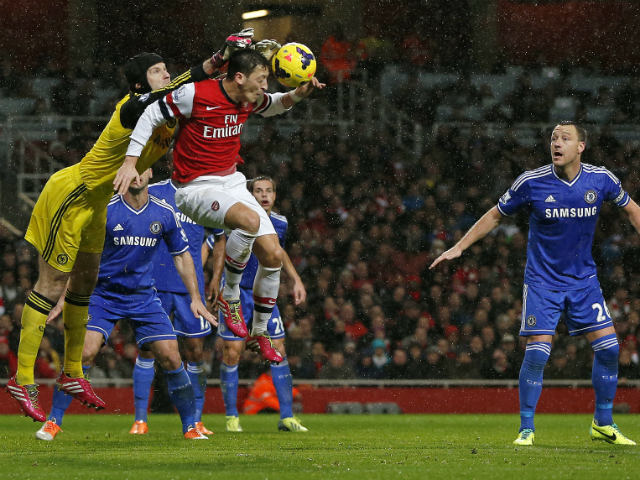 Chelsea's Czech goalkeeper Petr Cech challenges Arsenal's German midfielder Mesut Ozil during the English Premier League football match between Arsenal and Chelsea at the Emirates Stadium in London on December 23, 2013