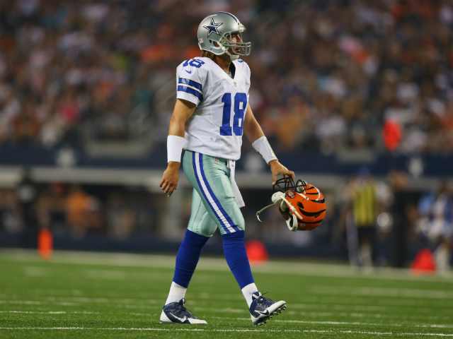 Kyle Orton #18 of the Dallas Cowboys picks up the helmet for Brandon Thompson #98 of the Cincinnati Bengals during a preseason game at AT&T Stadium on August 24, 2013
