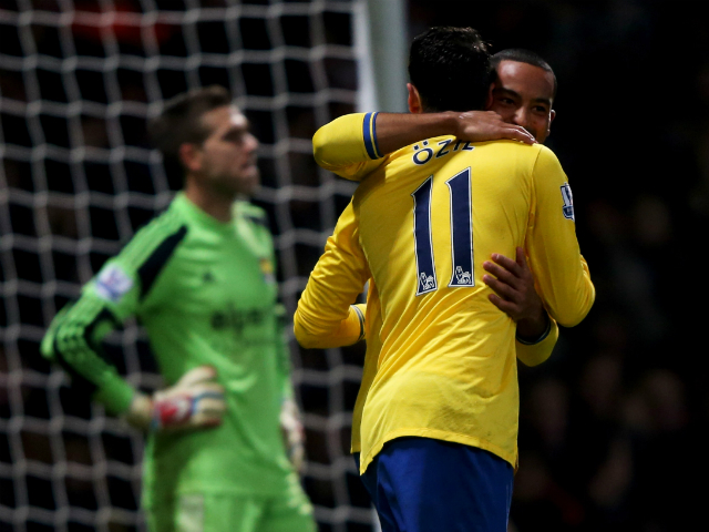 Theo Walcott of Arsenal celebrates with Mesut Ozil as he scores their first goal during the Barclays Premier League match between West Ham United and Arsenal at Boleyn Ground on December 26, 2013