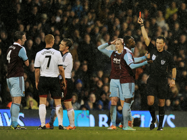 Kevin Nolan of West Ham is shown the red card by Referee Mark Clattenburg during the Barclays Premier League match between Fulham and West Ham United at Craven Cottage on January 1, 2014