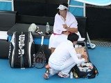 Laura Robson of Great Britain is treated by a trainer for a wrist injury in her first round match against Yanina Wickmayer of Belgium during day two of the Moorilla Hobart International at Domain Tennis Centre on January 6, 2014