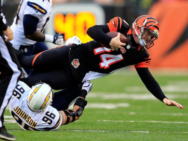 Quarterback Andy Dalton of the Cincinnati Bengals is sacked by outside linebacker Jarret Johnson of the San Diego Chargers during a Wild Card Playoff game on January 5, 2014