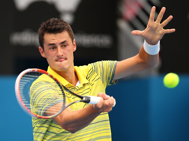 Bernard Tomic of Australia plays a forehand in his first round match against Marcel Granollers of Spain during day three of the 2014 Sydney International at Sydney Olympic Park Tennis Centre on January 7, 2014