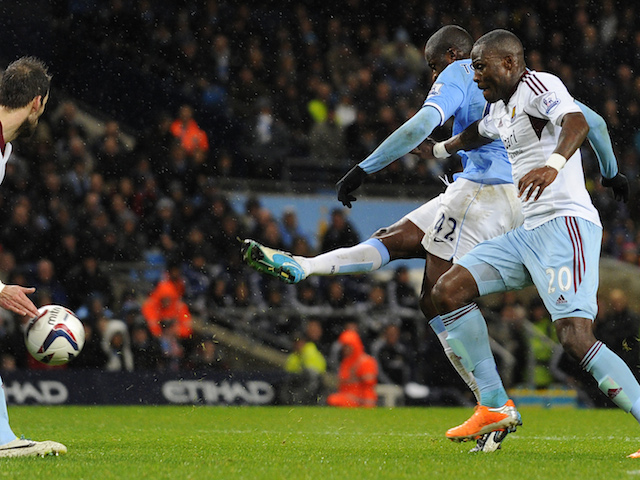 Manchester City's Ivorian midfielder Yaya Toure (2R) scores his team's third goal as West Ham United's Ivorian defender Guy Demel (R) defends during the English League Cup semi-final on January 8, 2014