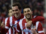 Atletico Madrid's forward David Villa celebrates with Atletico Madrid's Uruguayan defender Diego Godin after scoring during the Spanish league football match Club Atletico de Madrid vs Sevilla FC at the Vicente Calderon stadium in Madrid on January 19, 20