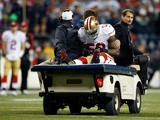 Linebacker NaVorro Bowman #53 of the San Francisco 49ers is carted off the field in the fourth quarter against the Seattle Seahawks during the 2014 NFC Championship at CenturyLink Field on January 19, 2014