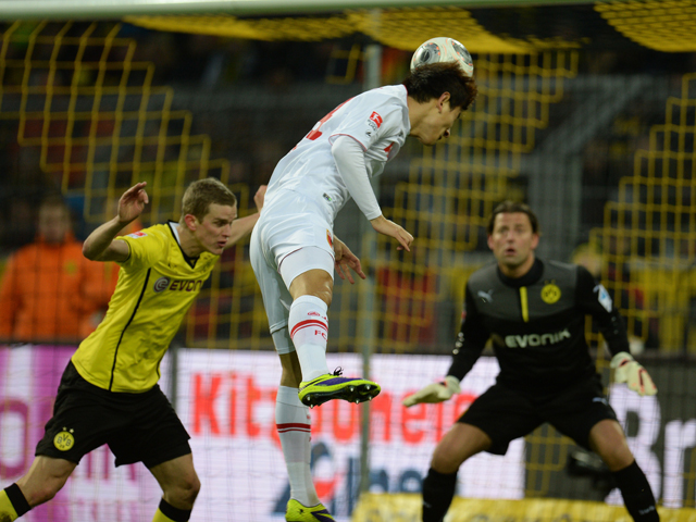 FC Augsburg's Korean forward Ji Dong Won scores against Dortmund's midfielder Sven Bender and Dortmund's goalkeeper Roman Weidenfeller during the German first division Bundesliga football match Borussia Dortmund vs FC Augsburg in the German city of Dortmu
