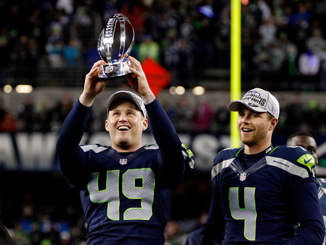 Clint Gresham #49 and kicker Steven Hauschka #4 of the Seattle Seahawks celebrate with the George Halas Trophy after the Seahawks 23-17 victory against the San Francisco 49ers during the 2014 NFC Championship at CenturyLink Field on January 19, 2014