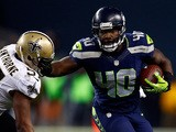 Fullback Derrick Coleman #40 of the Seattle Seahawks carries the ball as outside linebacker David Hawthorne #57 of the New Orleans Saints defends during a game on December 2, 2013