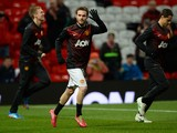 Manchester United's Spanish midfielder Juan Mata waves as he runs onto the pitch to warm-up ahead of the English Premier League football match between Manchester United and Cardiff City at Old Trafford in Manchester, northwest England, on January 28, 2014