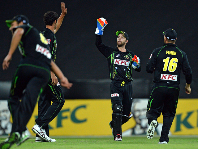 Australian cricketers celebrate the dismissal of England's batsman Luke Wright during the third cricket T20 international series match in Sydney on February 2, 2014