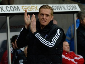 Swansea's new head coach Garry Monk greets fans ahead of the match against Cardiff during their Premier League match on February 8, 2014