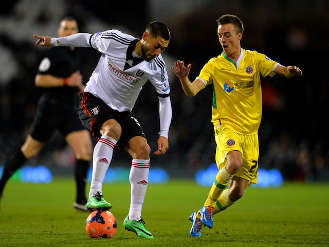 Clint Dempsey of Fulham ais marshalled by Stefan Scougall of Sheffield United during the FA Cup Fourth Round Replay match against Sheffield United on February 4, 2014