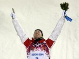 Canada's gold medallist Alex Bilodeau celebrates on the podium during the flower ceremony for the Men's Freestyle Skiing Moguls final at the Rosa Khutor Extreme Park on February 10, 2014