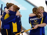 Sweden's women's curling team celebrate after winning the round robin session 10 match against Russia at the Ice Cube curling centre in Sochi on February 16, 2014