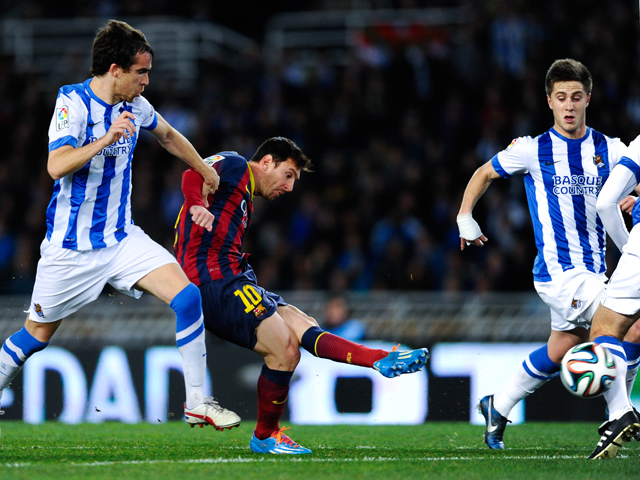 Lionel Messi of FC Barcelona scores the opening goal next to Mikel Gonzalez Martinez of Real Sociedad during the Copa del Rey Semi Final second leg between Real Sociedad and FC Barcelona at Anoeta Stadium on February 12, 2014