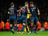 Thomas Muller of Bayern Munchen celebrates with Toni Kroos and Philipp Lahm of Bayern Munchen after scoring the second goal during the UEFA Champions League Round of 16 first leg match between Arsenal and FC Bayern Munchen at Emirates Stadium on February
