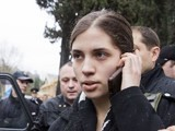 A members of Russian punk group Pussy Riot, Nadezhda Tolokonnikova, speaks by her cell phone, as she is escorted to a police car after being detained in the Adler district of Sochi, on February 18, 2014
