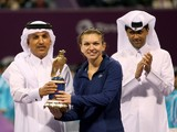 Simona Halep of Romania holds her trophy next to Qatari Minister of Finance Ali Sharif al-Emadi and president of the Qatar Tennis Federation Nasser al-Khelaifi, after winning the Qatar Open final tennis match against Angelique Kerber of Germany on Februar
