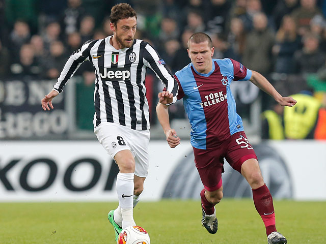 Juventus' Claudio Marchisio and Trabzonspor's Alexandru Bourceanu in action during their Europa League match on February 20, 2014