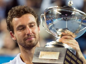 Latvia's Ernests Gulbis looks at his trophy after defeating France's Jo-Wilfried Tsonga during their Open 13 ATP tennis tournament final match on February 23, 2014