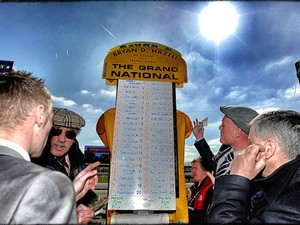 A bookmaker takes bets on the Grand National at Aintree racecourse on April 06, 2013