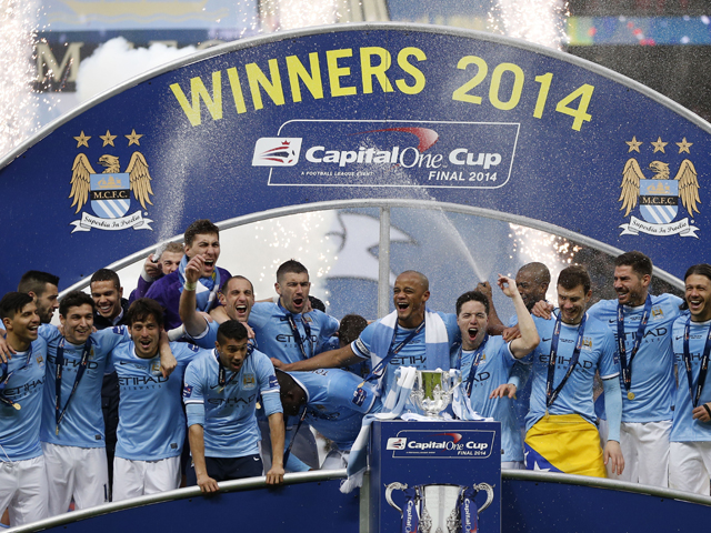 Manchester City players pose together with the League Cup after winning the final football match between Manchester City and Sunderland at Wembley Stadium in London on March 2, 2014