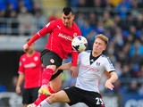 Cardiff City player Gary Medel challenges Cauley Woodrow of Fulham during the Barclays Premier league match between Cardiff City and Fulham at Cardiff City Stadium on March 8, 2014