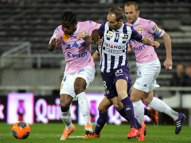 Toulouse's French midfielder Etienne Didot (C) vies for the ball with Evian's Ivoirian midfielder Eric Tie Bi during the French L1 football match on March 22, 2014