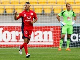 Marcelo Carrusca of Adelaide United celebrates after scoring a goal while Glen Moss of the Phoenix looks on during the round 25 A-League match between Wellington Phoenix and Adelaide United at Westpac Stadium on March 30, 2014