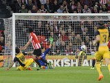 Atletico Madrid's Brazilian forward Diego da Silva Costa scores past Athletic Bilbao's goalkeeper Gorka Iraizoz during the Spanish league football match Athletic Club Bilbao vs Atletico Madrid at the San Mames stadium in Bilbao on March 29, 2014