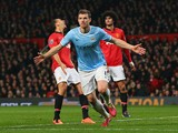 Edin Dzeko of Manchester City celebrates scoring the second goal during the Barclays Premier League match between Manchester United and Manchester City at Old Trafford on March 25, 2014