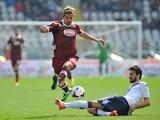 Alessio Cerci of Torino FC is challenged by Davide Astori of Cagliari Calcio during the Serie A match between Torino FC and Cagliari Calcio at Stadio Olimpico di Torino on March 30, 2014