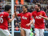 Shinji Kagawa and Juan Mata of Manchester United congratulate Javier Hernandez of Manchester United on scoring their third goal during the Barclays Premier League match between Newcastle United and Manchester United at St James' Park on April 5, 2014