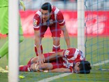 Koke of Club Atletico de Madrid conforts teammate Diego Costa after Costa knocked his knee off the goalposts while scoring Atletico's 2nd goal against Getafe on April 13, 2014
